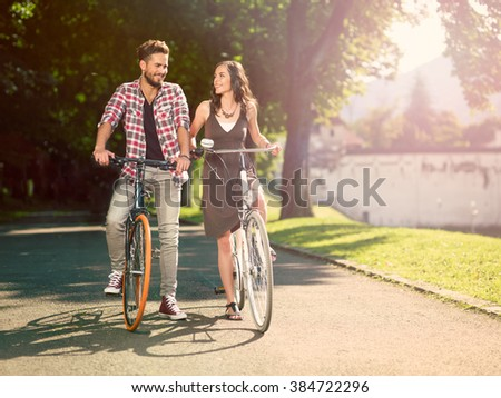 smiling couple on the bike in an alley with green trees on a sunny summer day - stock photo