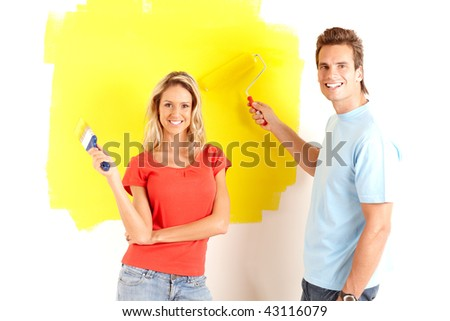 smiling couple painting interior wall of home. - stock photo