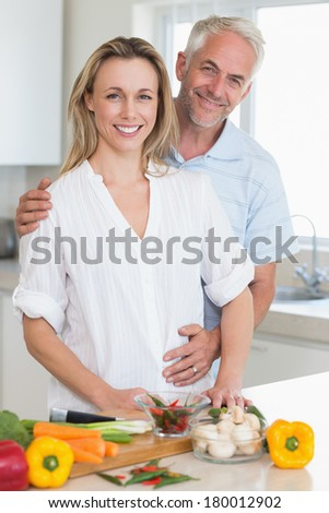 Smiling couple preparing a healthy dinner together at home in the kitchen - stock photo