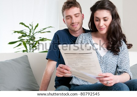 Smiling couple reading a bill arrived via mail - stock photo