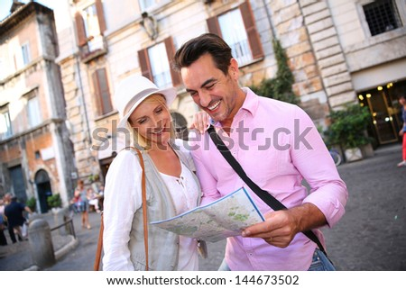 Smiling couple reading city map in the streets of Rome