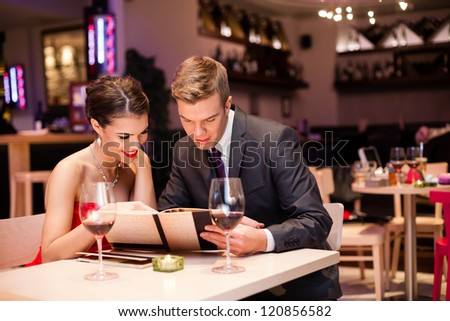Smiling couple reading menu  and choosing meal - stock photo
