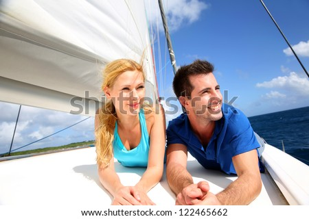 Smiling couple relaxing on a yacht by sunny day - stock photo