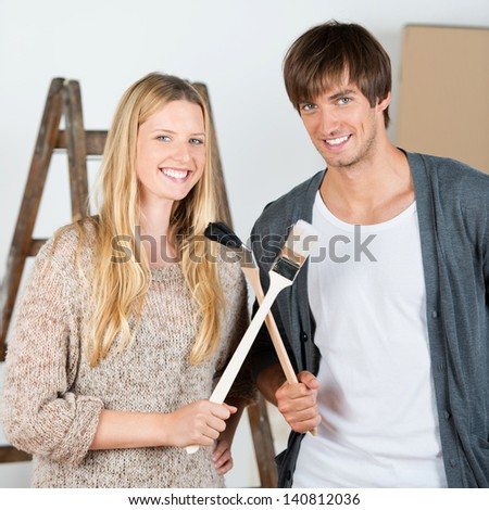 smiling couple renovating home and crossing brushes - stock photo