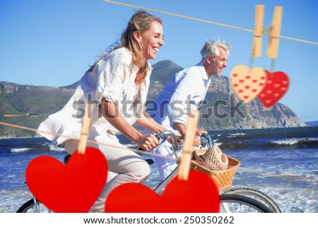 Smiling couple riding their bikes on the beach against hearts hanging on the line - stock photo
