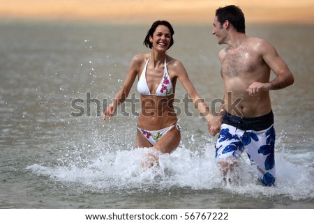 Smiling couple running in the sea