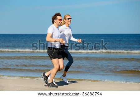 Smiling couple running on the beach - stock photo