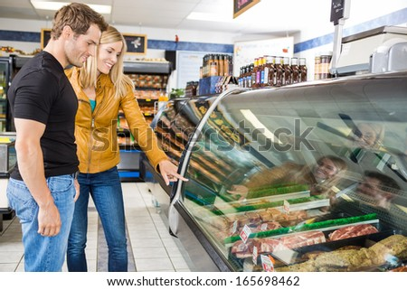 Smiling couple selecting meat from display cabinet at butcher's shop - stock photo