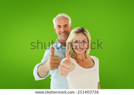 Smiling couple showing thumbs up together against green vignette - stock photo