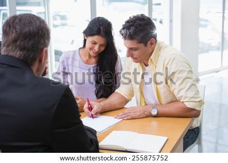 Smiling couple signing a contract at new car showroom - stock photo