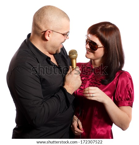 smiling couple singing into a microphone on a white background