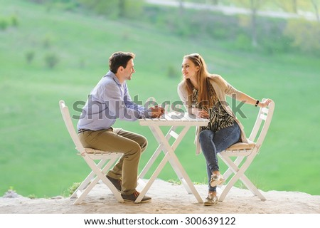 smiling couple sitting at table  - stock photo