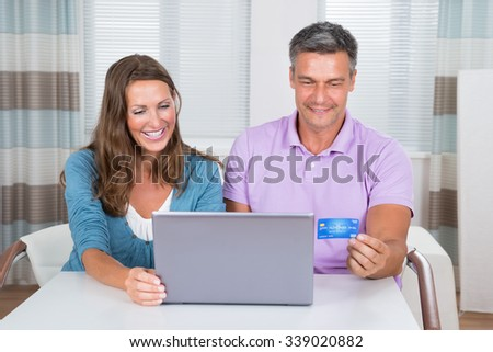 Smiling Couple Sitting In Living Room Shopping Online On Laptop - stock photo