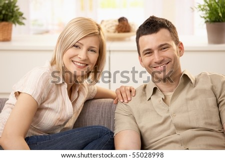Smiling couple sitting on couch in sunny living room. - stock photo