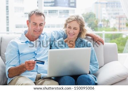 Smiling couple sitting on their couch using the laptop to buy online at home in the sitting room - stock photo