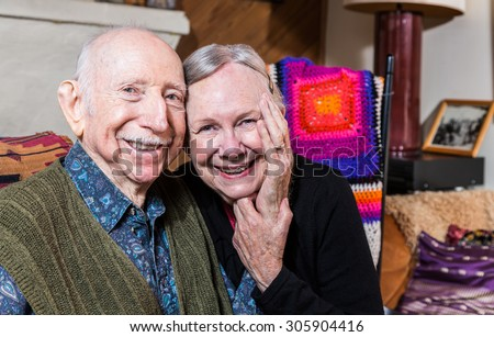 Smiling couple sitting together in living-room touching hands - stock photo