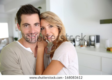 Smiling couple standing in new home ktichen - stock photo