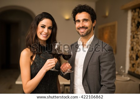 Smiling couple toasting wineglasses - stock photo