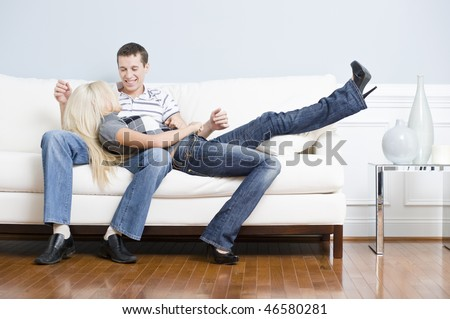Smiling couple together on white couch, with woman reclining with her head in the man's lap. Horizontal format. - stock photo