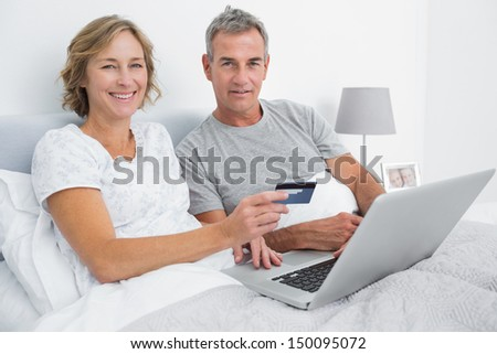 Smiling couple using their laptop to buy online in bed looking at camera at home in bedroom - stock photo