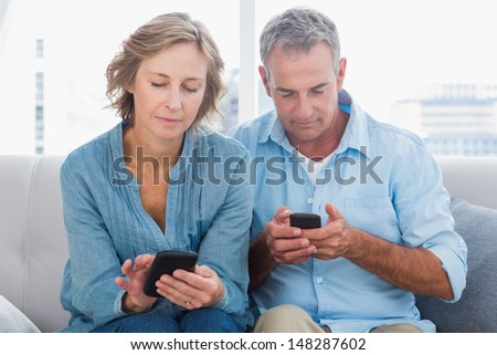 Smiling couple using their smartphones at home in the living room