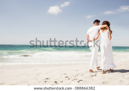 Smiling couple walking together on the beach
