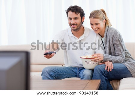 Smiling couple watching TV while eating popcorn in their living room