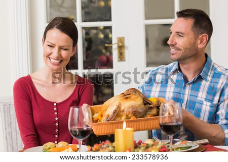 Smiling couple while man holding rast turkey at home in the living room - stock photo