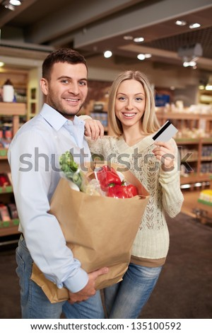 Smiling couple with a credit card - stock photo