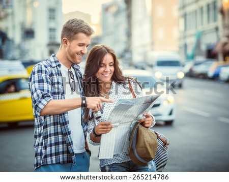 Smiling couple with a map in the city - stock photo