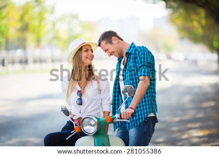 Smiling couple with a scooter outdoors - stock photo