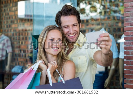 Smiling couple with shopping bags taking selfies at shopping mall