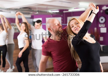 Smiling couples enjoying of partner dance indoor - stock photo
