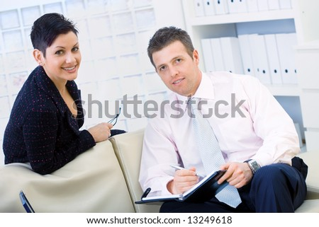 Smiling coworkers, businessman and businesswoman sitting on sofa and working together at office, doing paperwork.