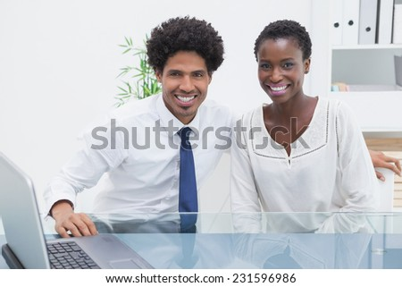 Smiling coworkers sitting and looking at camera in the office