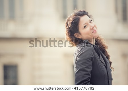 smiling curly woman in cityscape