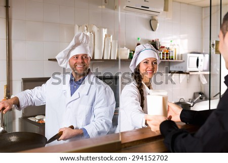 Smiling customer, chef and cook at fastfood place - stock photo