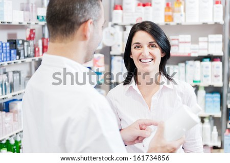 Smiling customer hand handsome pharmacist. The are in a real pharmacy