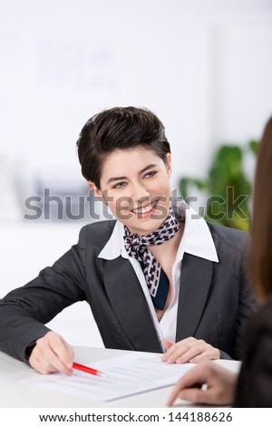 Smiling customer relations supervisor with a lovely friendly smile assisting a customer in completing a form - stock photo