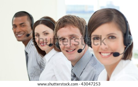 Smiling customer service agents with headset on in a call center