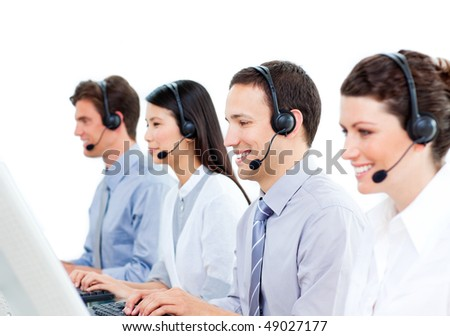 Smiling customer service agents working in a call center against a white background - stock photo