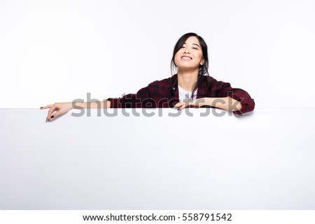 smiling cute asian young woman behind an empty white board casual dressed, isolated on white