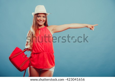 Smiling cute attractive young woman girl in red shirt and hat in studio on blue showing blank empty copyspace. Summer female fashion and advertisement. - stock photo