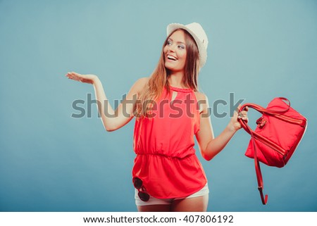 Smiling cute attractive young woman girl in red shirt and hat with handbag and sunglasses in studio on blue showing blank empty copyspace on open palm. Summer female fashion and advertisement. - stock photo