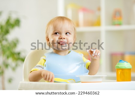 smiling cute baby kid boy eating itself with spoon - stock photo