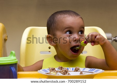 smiling cute child baby boy eating itself with spoon