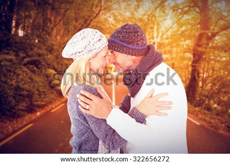 Smiling cute couple romancing over white background against country road - stock photo
