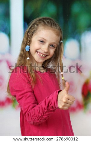 Smiling cute girl shows thumbs up - all will be good - positive lifestyle concept - focus on  face - stock photo