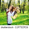 Smiling cute girl with long hair dancing in green park - stock photo
