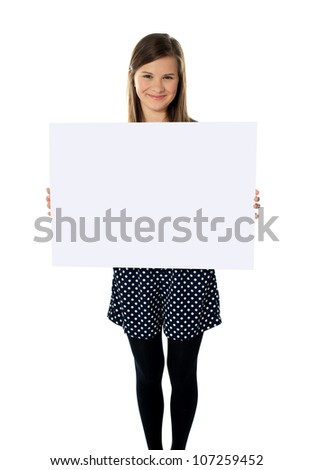 Smiling cute isolated girl displaying blank white poster - stock photo